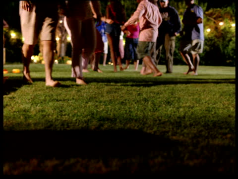Pan left past people dancing and lying on picnic blanket in garden at party