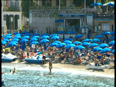 vídeos de stock e filmes b-roll de pan left past people under blue and yellow parasols on very crowded beach and people in sea or on pedalos - 1995