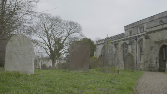 pan left shot from the porch of the church of st mary the virgin to the tombstones at the churchyard - death stock videos & royalty-free footage