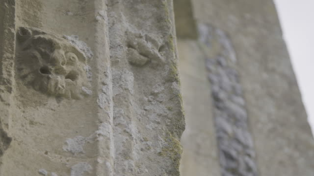 pan left shot of a gothic style carved face on the side of the church of st mary in troston - england stock videos & royalty-free footage