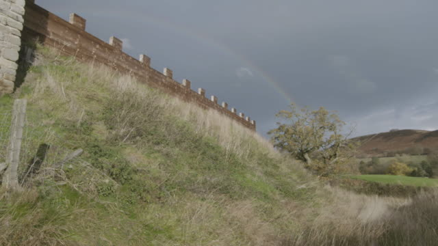 pan left shot of a reconstructed wooden wall at the vindolanda roman fort with a rainbow in the background - uncultivated stock videos & royalty-free footage