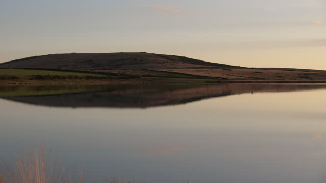 pan left shot of dozmary pool in cornwall at sunset - literature stock videos & royalty-free footage