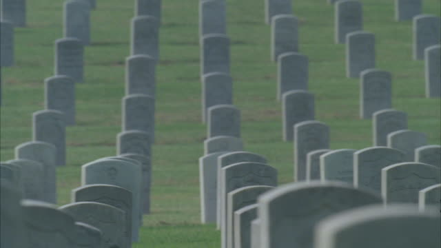 pan left shot of rows of white tombstones in a military veteran's cemetery. - grab stock-videos und b-roll-filmmaterial