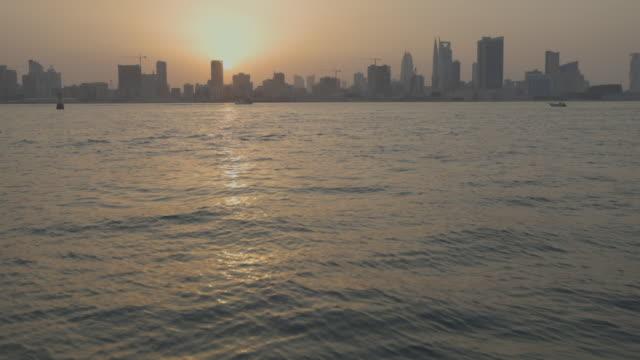 pan left shot of the manama skyline at sunset. - ペルシャ湾点の映像素材/bロール