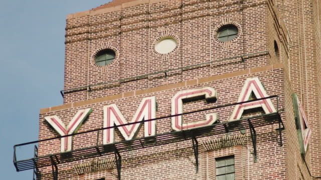 pan left shot of the neon sign on the top of the harlem ymca - african american culture stock videos & royalty-free footage