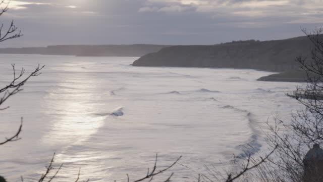 vídeos de stock, filmes e b-roll de pan left shot of the waving sea at the scarborough bay - scarborough norte de yorkshire
