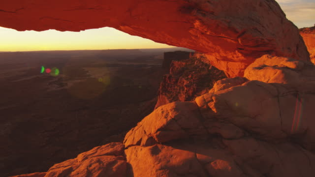 pan left, sun rises in arches national park - natural arch stock videos & royalty-free footage