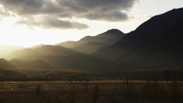 pan left, sunset over mountains in japan - wide stock-videos und b-roll-filmmaterial