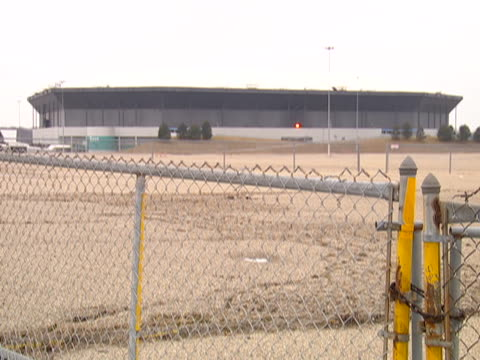 pan left to a wide shot of an empty parking lot of the pontiac silverdome in pontiac, michigan. - ポンティアック点の映像素材/bロール