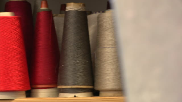 pan left to a woman taking red yarn from a shelf - ball of wool stock videos & royalty-free footage