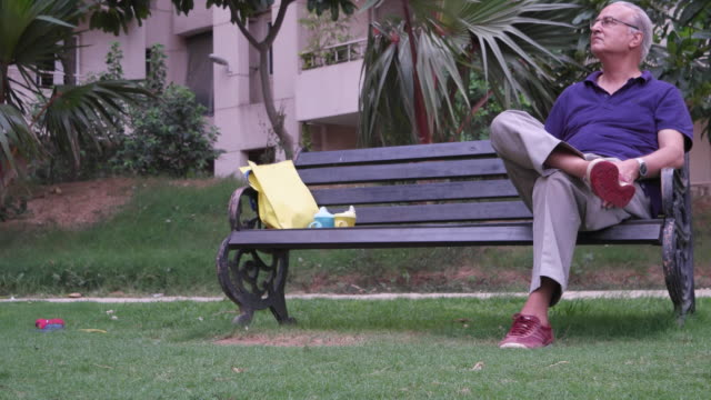 pan left to an elderly gentleman sitting in a public park on a bench - ベンチ点の映像素材/bロール