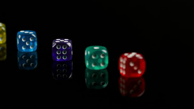 pan left to colourful dice on black surface - cube stock videos & royalty-free footage