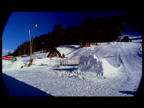 pan left to follow snowboarder who makes huge jump from ramp across snow o'neill freestyle jam davos switzerland - eskapismus stock-videos und b-roll-filmmaterial