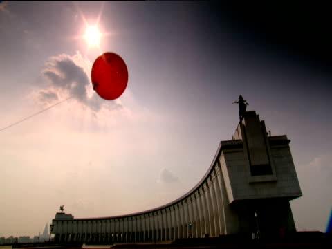 vídeos de stock e filmes b-roll de pan left to red balloon blowing in front of moscow war memorial - memorial de guerra