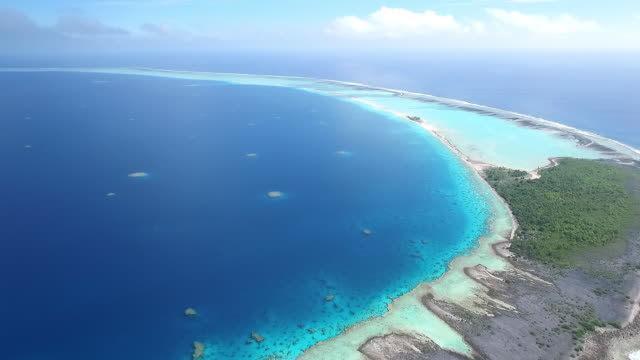 Pan left to reveal entire atoll and coral lagoon of Motutunga
