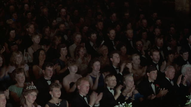 Pan left to right across formally dressed audience in large theater. Audience begins clapping, rises to standing ovation. Ovation is dying down when shot ends. Could be opera, ballet, awards ceremony, theatrical event.