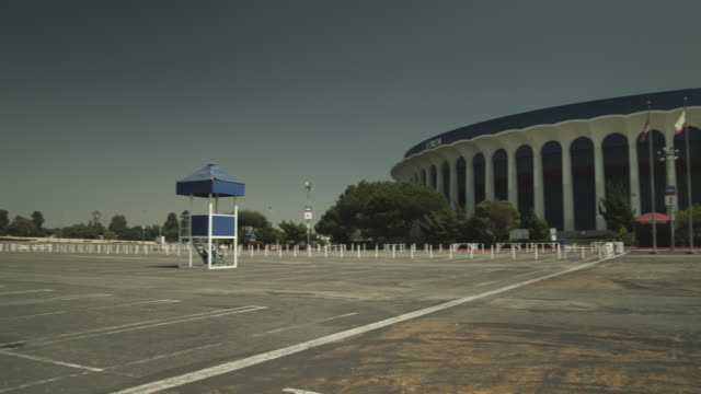 pan left to right across parking lot to the forum stadium. sign visible in bg. - inglewood video stock e b–roll