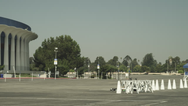 pan left to right across parking lot to the forum stadium. - inglewood video stock e b–roll