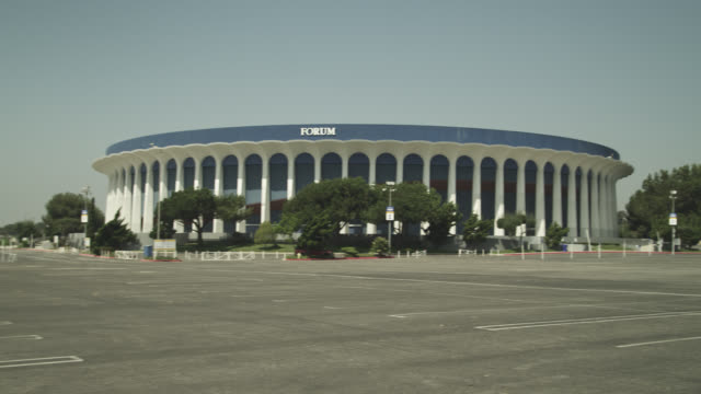 pan left to right across the forum stadium or arena. parking lot empty. - inglewood video stock e b–roll