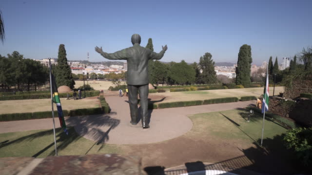 pan left to right: big famous statue of nelson mandela happily explored by tourists of the area - pretoria, south africa - statue stock videos & royalty-free footage