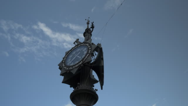 pan left to right: clock with statues on top contrasted by the sky background of the city - kazan, russia - 郵便点の映像素材/bロール