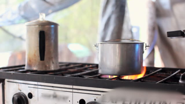 pan left to right: cooking in the campsite - kitchenware shop stock videos & royalty-free footage