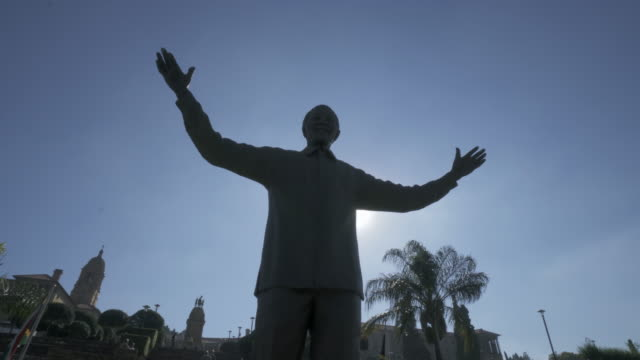 pan left to right: famous statue of nelson mandela with sun at the background with city building in the back - pretoria, south africa - statue stock videos & royalty-free footage