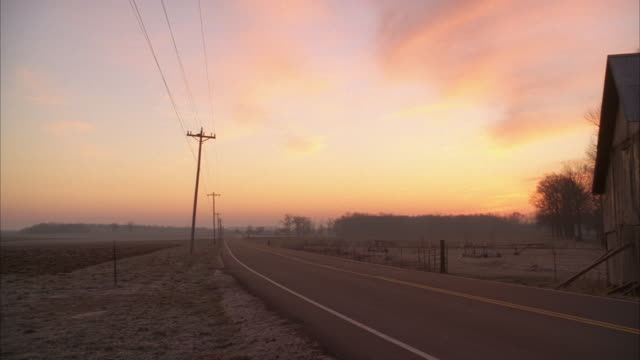 pan left to right from countryside or farmland at dawn to country road as pickup truck drives by. telephone poles and wires visible. barn visible in fg. beautiful pink sky. rural area.