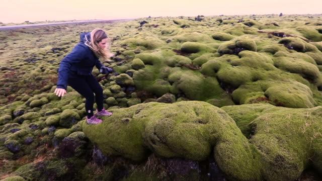 vídeos de stock e filmes b-roll de pan left to right: girl on top of slippery rock - islândia