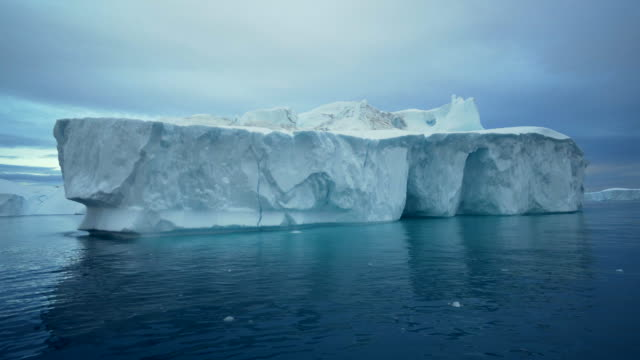 pan left to right: iceberg of greenland disko bay surrounded by glaciers - iceberg ice formation stock videos & royalty-free footage