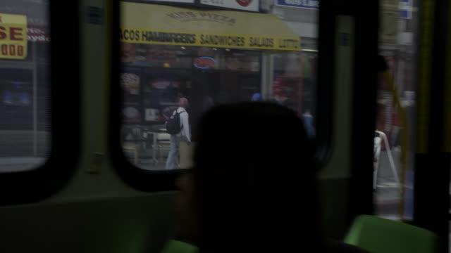 vídeos y material grabado en eventos de stock de pan left to right moving pov from bus driving through city streets. broadway. passengers. - señal de stop