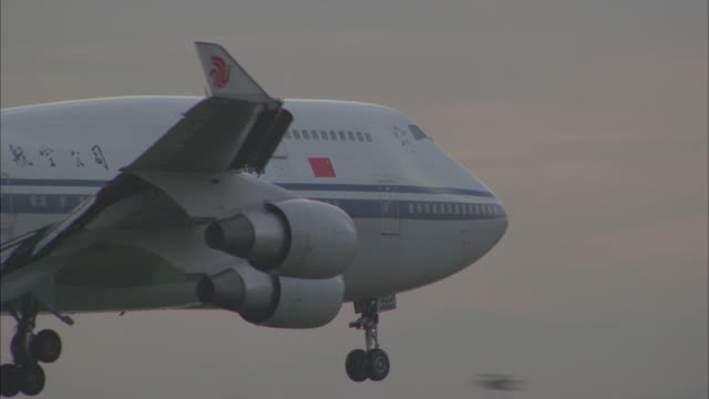 pan left to right of air china, commercial airliner, jet or airplane landing on runway of airport.