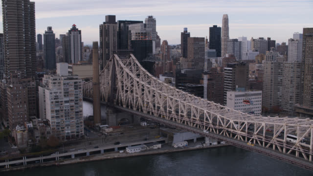 pan left to right of black suv driving across queensboro bridge. east river and city skyline partially visbile.