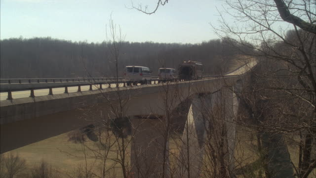 stockvideo's en b-roll-footage met pan left to right of vans and tour bus or rv driving on natchez trace parkway bridge through wooded area or forest. bare branches on trees. countryside or rural area. - dubbeldekker bus