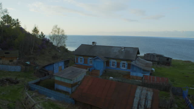 vidéos et rushes de pan left to right: remote beautiful home near the relaxing shores of the lake passed by a train - lake baikal, russia - endroit isolé