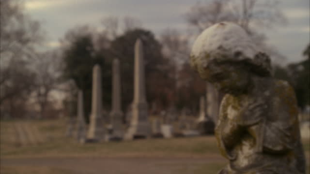 vídeos de stock, filmes e b-roll de pan left to right to stone figurine or statue of girl, could be on gravestone. graveyard or cemetery. bare branches on trees. - figura feminina