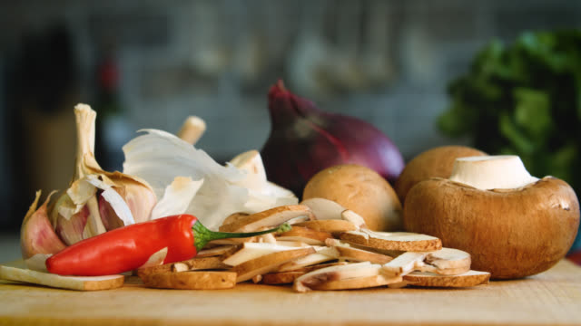 Pan left to various vegetables piled up on a chopping board