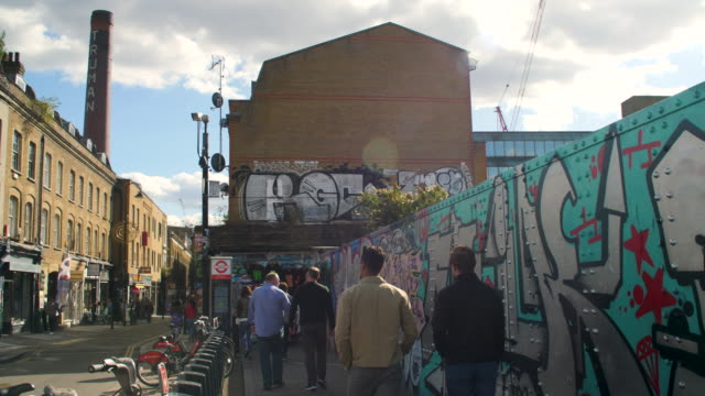 pan left to wide view of brick lane on a sunny day - poster stock-videos und b-roll-filmmaterial