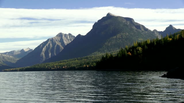 pan left wide shot of mountain lake with rocky shoreline and jagged peaks in background. - seeufer stock-videos und b-roll-filmmaterial