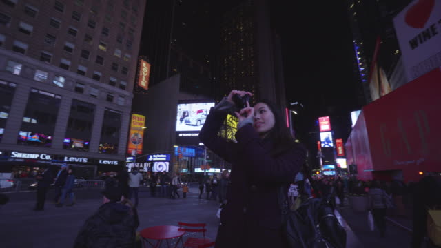 pan left, woman takes photographs in times square - one night stand stock videos & royalty-free footage