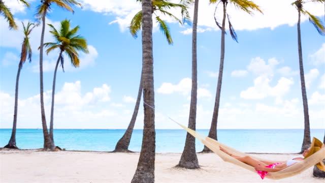 ws pan left, young woman lying in hammock at tropical beach - auf dem rücken liegen stock-videos und b-roll-filmmaterial