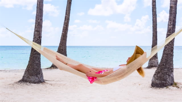 CU pan left, young woman lying in hammock at tropical beach