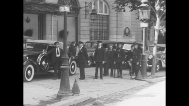pan line of cars parked diagonally with chauffeurs soldiers and others stand in group / ms chauffeur by car pan to man talking to chauffeur / cars on... - the spanish donkey stock videos & royalty-free footage