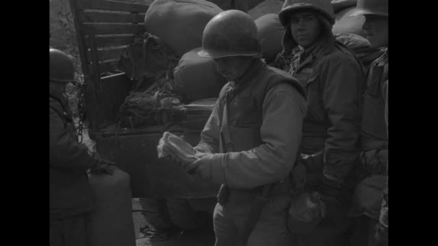 pan line of casual american soldiers wearing army issue winter clothing and helmets and duffel bags at rear / vs soldier examining a pair of thick... - korean war stock videos & royalty-free footage