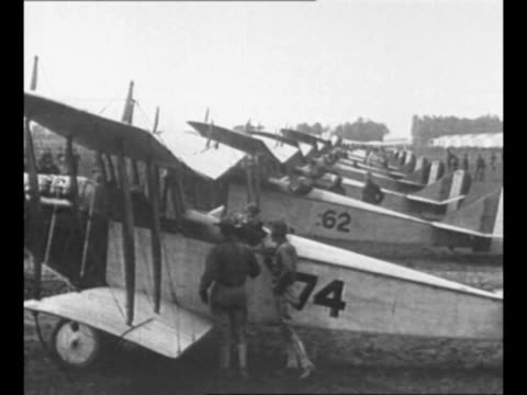 pan line of military airplanes on field in 1917 smoke from propellers wafts by as men examine plane / plane takes off on field / col billy mitchell... - エディ リッケンバッカー点の映像素材/bロール