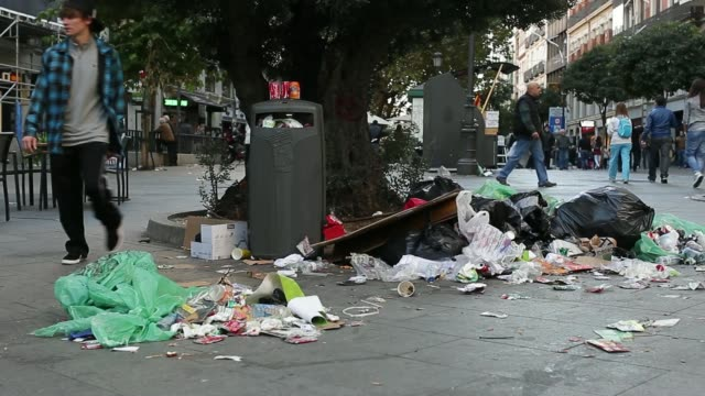 stockvideo's en b-roll-footage met pan l-r a pile of rubbish on a street on the tenth day of the cleaners' strike in madrid, spain, on thursday, nov. 14 various shots pedestrians pass... - gevuld