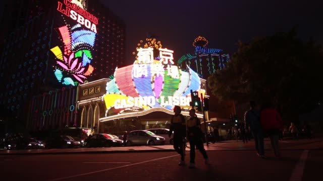 pan l-r, casino grand lisboa, operated by sjm holdings ltd., standing illuminated at night in macau, china, on thursday, march 12 pedestrians cross a... - ナイトイン点の映像素材/bロール
