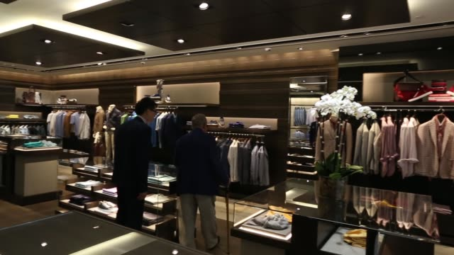 pan l-r interior of a canali holding spa store in hong kong, employees arrange merchandise inside a canali holding spa store, an employee arranges... - display cabinet stock videos & royalty-free footage