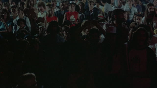 pan l-r of crowd at rock concert. see many people cheering, waving lighters, waving arms, and applauding. red light from stage reflecting off crowd.