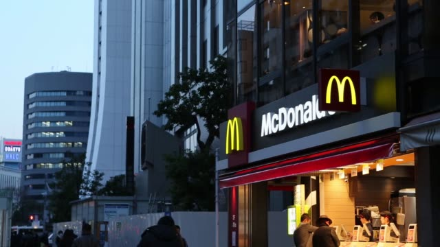 pan lr of mcdonald's signage above restaurant pedestrians walk past a mcdonald's restaurant operated by mcdonald's holdings co japan ltd in tokyo... - mcdonald's stock videos & royalty-free footage